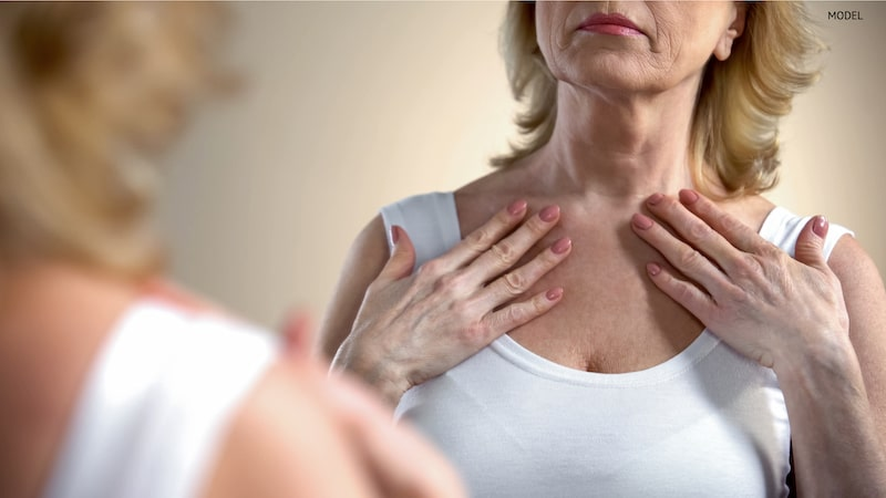 Older woman looking at herself in the mirror, noticing aging signs on her neck and collarbone