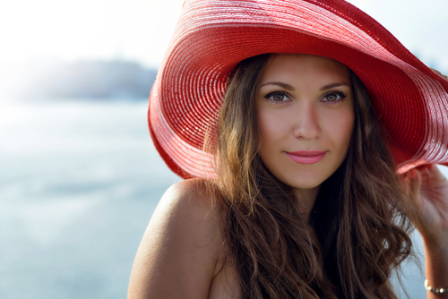 lady in a red hat smiling at the summer waterfront-img-blog