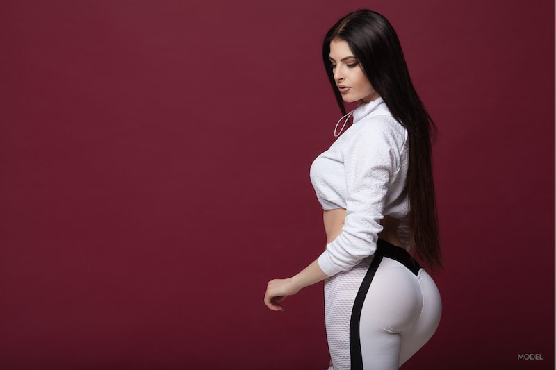 woman in leggings posing to show offer her buttocks on a maroon backdrop